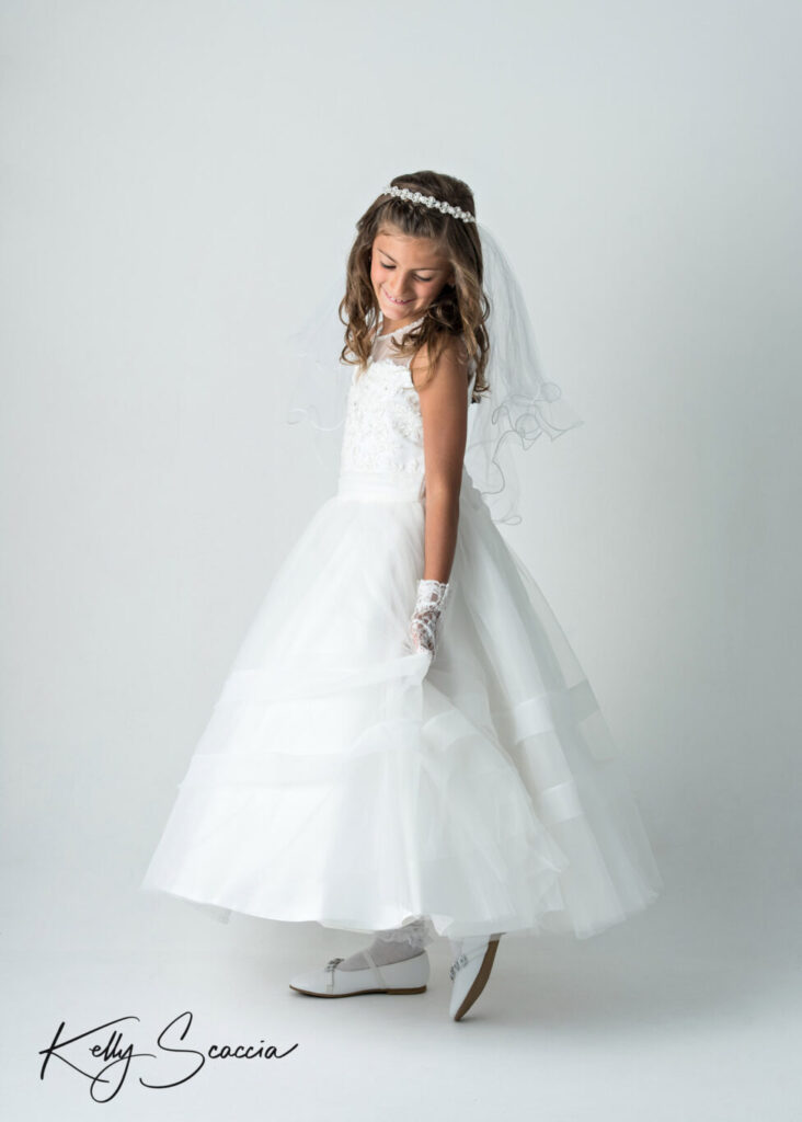 First Holy Communion girl studio portrait on a light background wearing a white dress, veil looking down over her shoulder spinning around