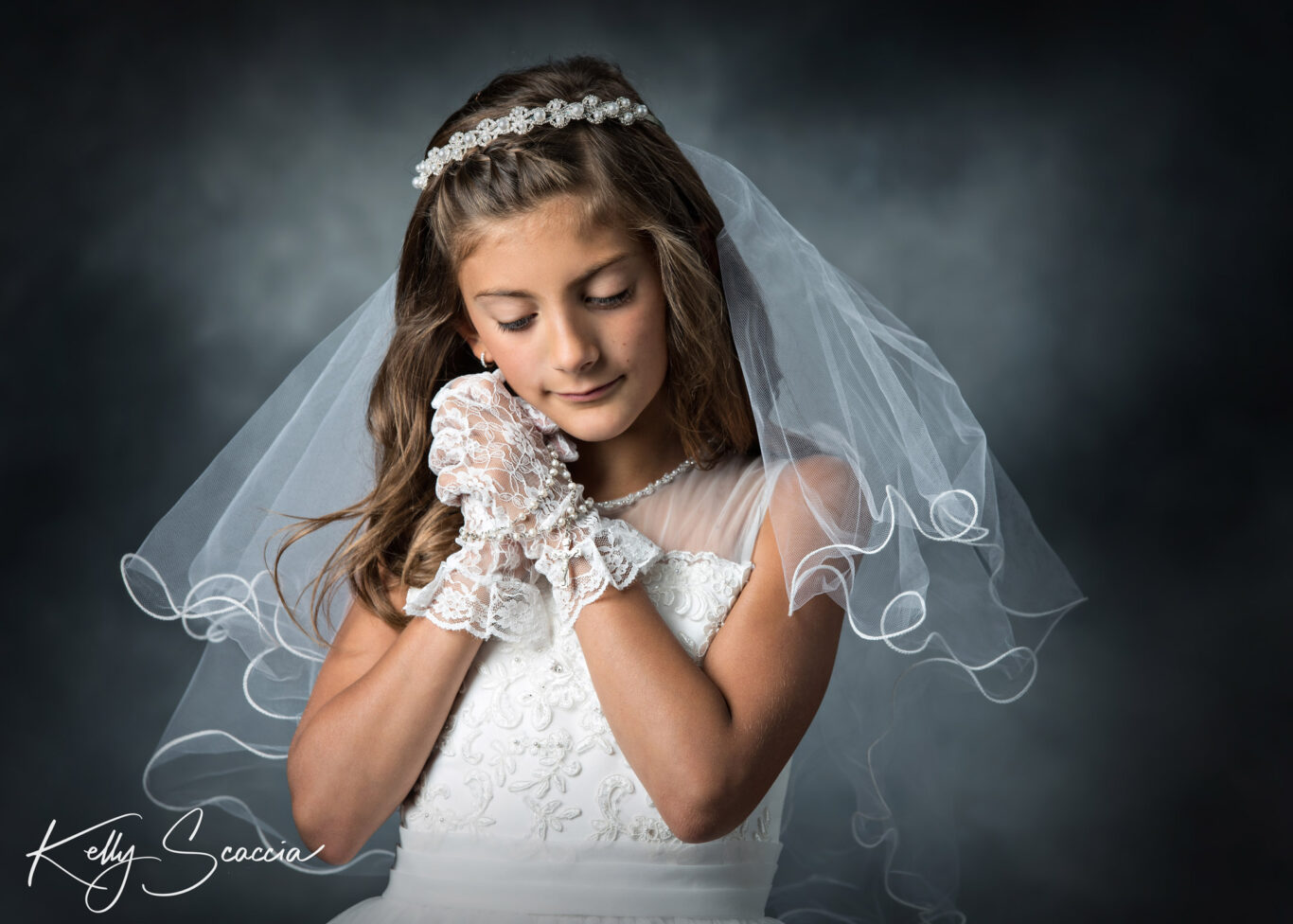 Studio First Holy communion girl portrait on a dark background wearing a white communion dress and veil hands under her chin eyes closed