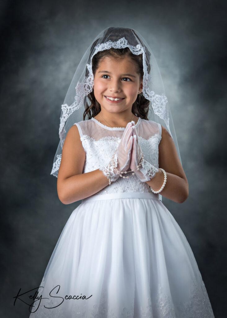 Studio girl first communion portrait wearing a white dress, veil smiling on a dark background, hands in prayer