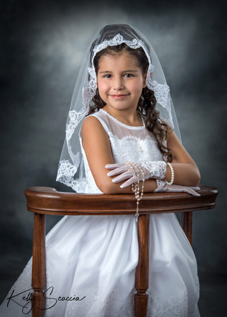 Studio girl first communion portrait wearing a white dress, veil smiling on a dark background, hands crossed in front of her on a kneeler