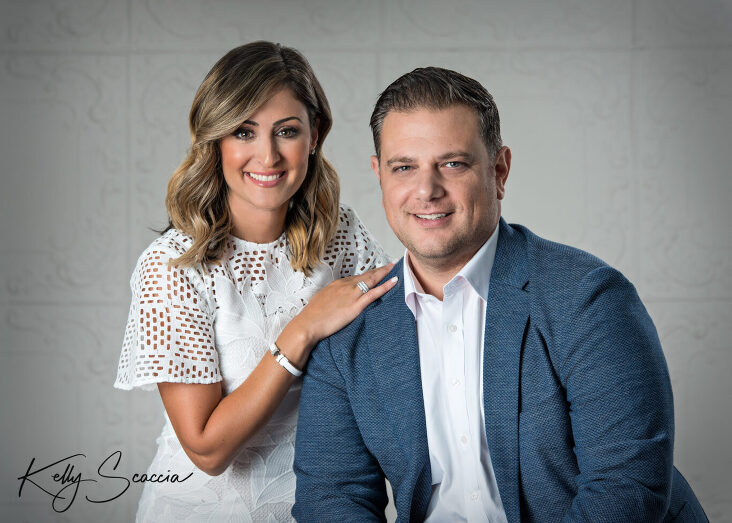 Husband and wife studio portrait on a light background wearing a white dress and sport coat smiling looking at you