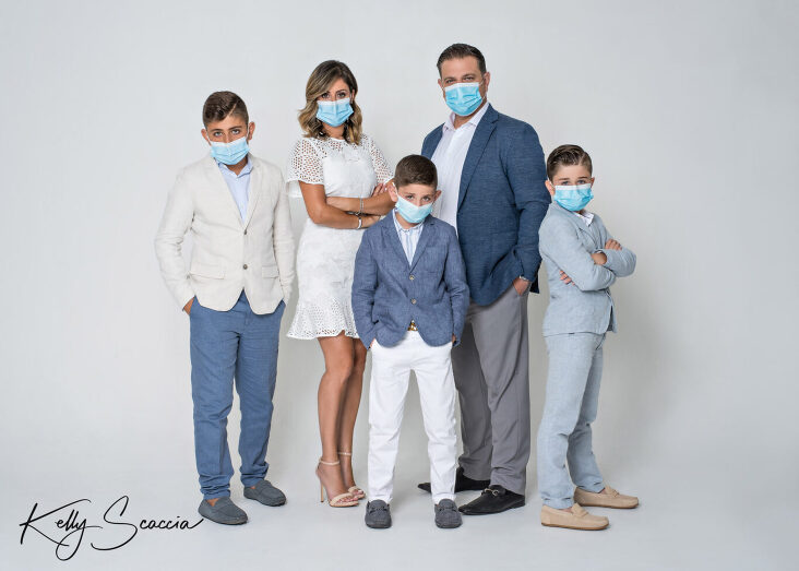 Family studio portrait on a light background mom in white dress, dad and three young boys wearing spot coats looking at you standing wearing COVID-19 masks