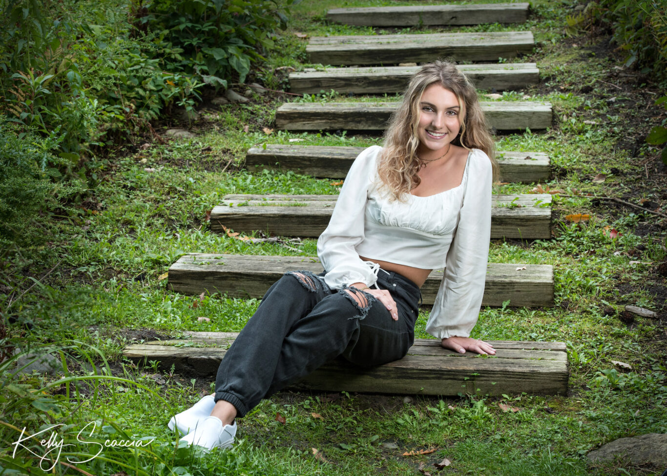 Senior girl outdoor portrait with long blonde hair, brown eyes looking at you wearing a cream shirt, black jeans smiling sitting on wood steps