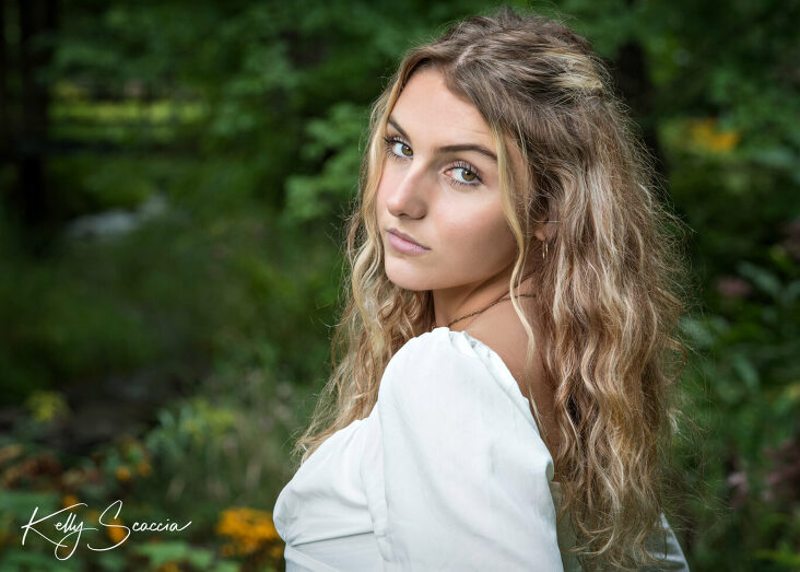Senior girl outdoor portrait with long blonde hair, brown eyes looking at you wearing a cream shirt, black jeans serious expression
