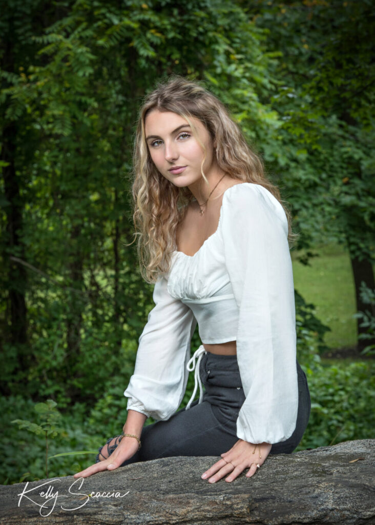 Senior girl outdoor portrait with long blonde hair, brown eyes looking at you wearing a cream shirt, black jeans sitting on a rock serious expression
