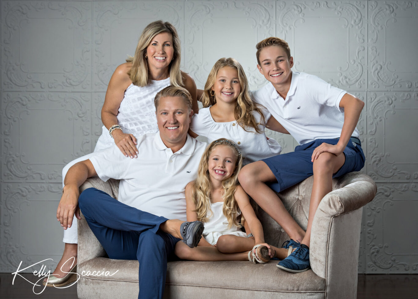 Studio family portrait of five, blonde hair, blue eyes, all in white and dad and son in blue shorts and pants sitting on a couch
