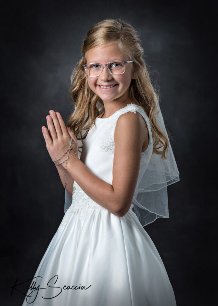 Communion girl studio portrait on a dark background wearing her white dress looking at you smiling with hands in prayer and rosary draped around them