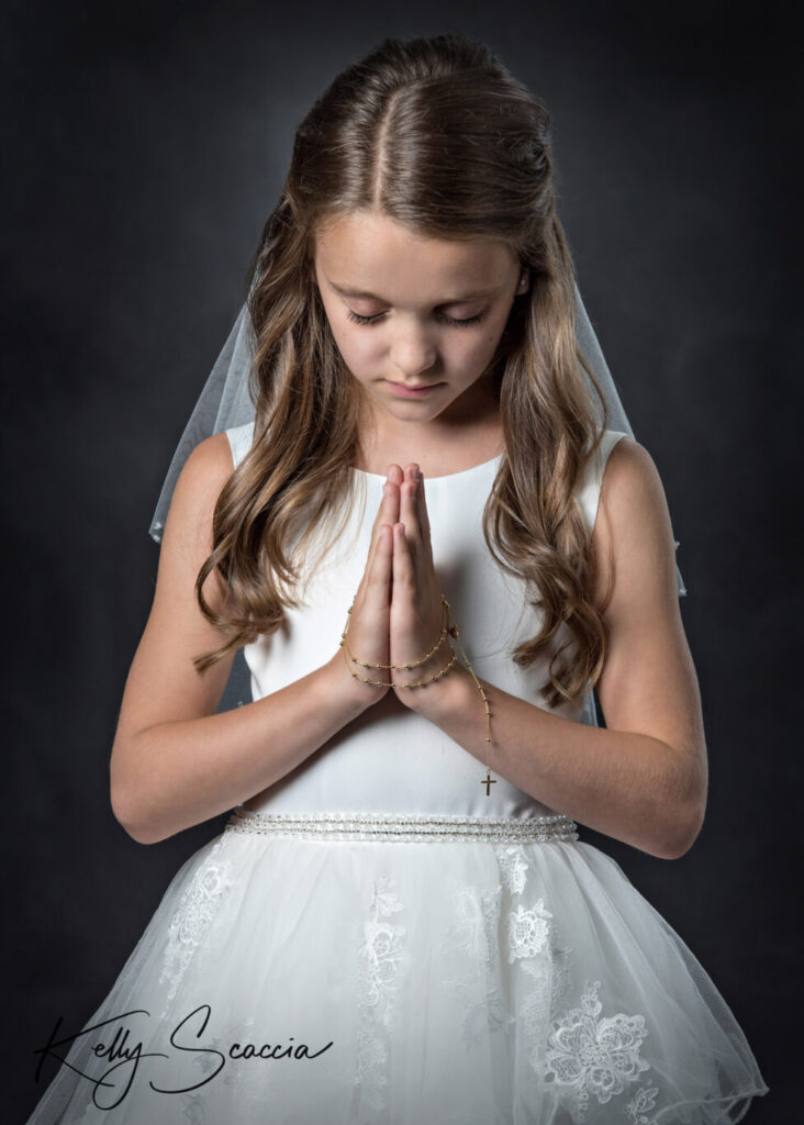 Communion girl studio portrait on a dark background wearing her white dress looking down at her praying hands