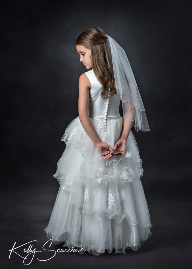 Communion girl studio portrait on a dark background wearing her white dress full length portrait back towards us with arms together behind her holding her rosary and looking down to her left profile