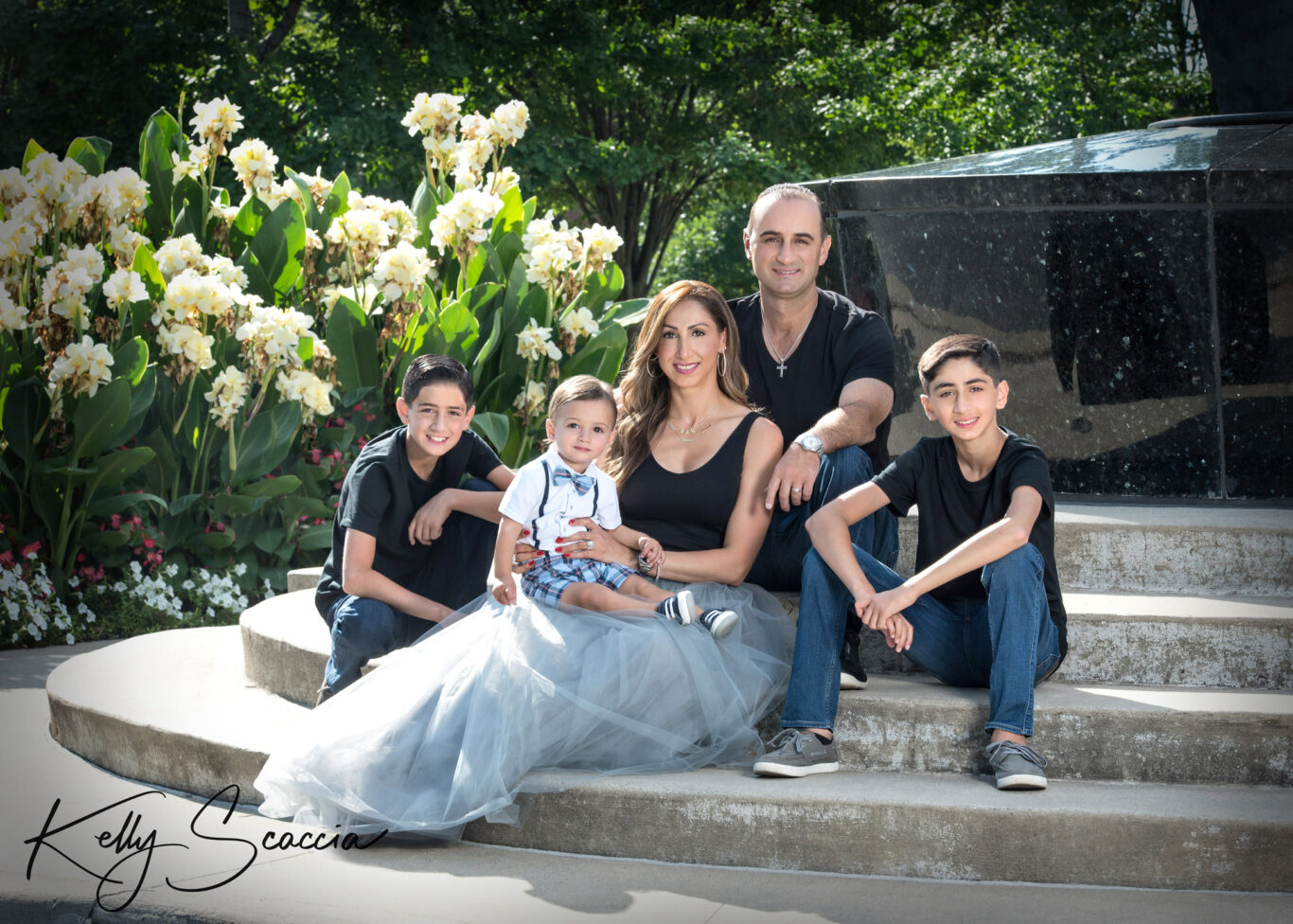 family of five outdoor portrait in black and jeans, mom in black top, gray skirt, baby boy in white shirt and checked shorts all looking and smiling at you