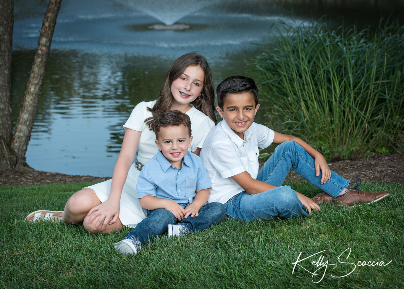 Big sister, little brothers outdoor portrait dressed in blues and whites smiling and looking at you