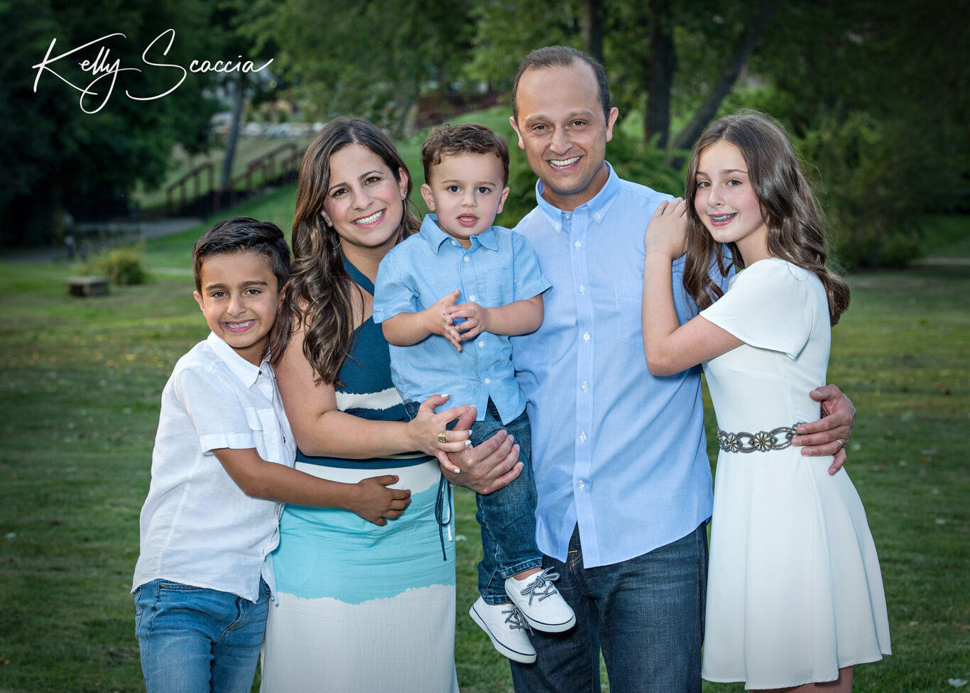 Outdoor family portrait in the park wearing blues and whites and smiling