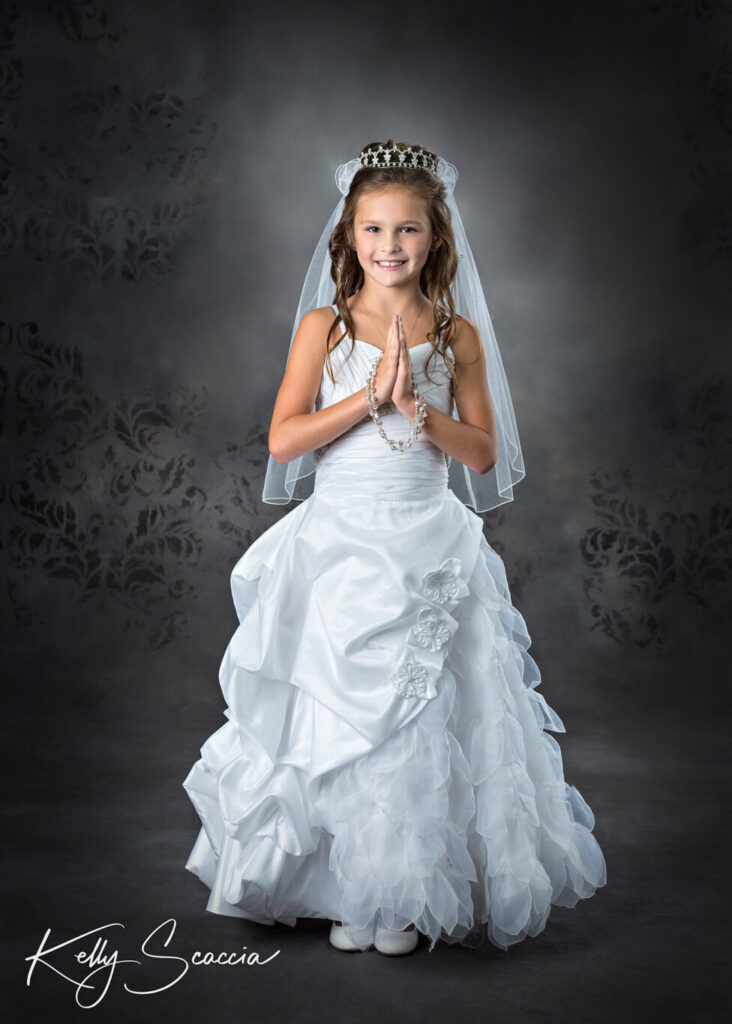 Studio portrait communion girl in dress and veil hands in prayer with rosary draped on them smiling at you
