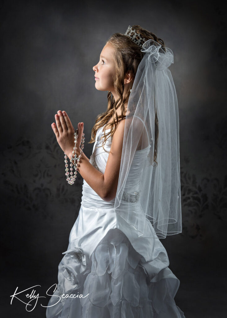 Studio portrait communion girl in dress and veil hands in prayer with rosary draped on them profile portrait looking up at light