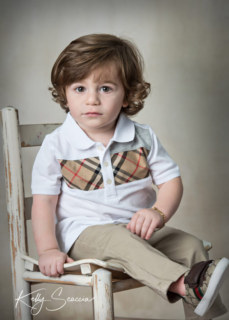 Studio portrait, little boy wearing white shirt, tan pants looking at you on a small chair