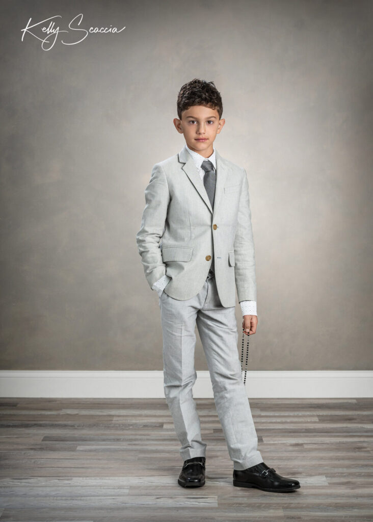 Studio communion boy portrait wearing light, gray suit, holding a rosary, looking at you, serious expression