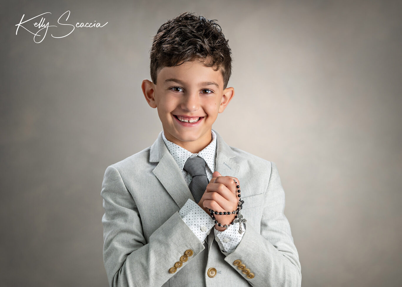Studio communion boy portrait wearing light, gray suit, holding a rosary, looking at you, smiling