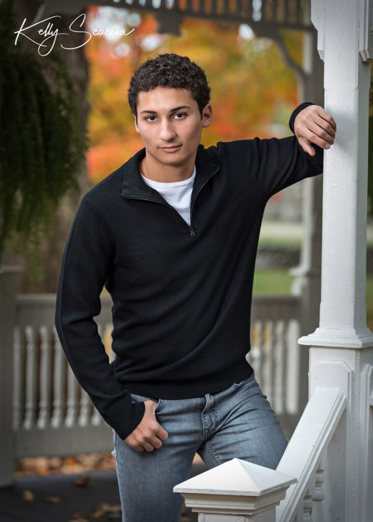 Outdoor senior guy portrait with short, dark, curly hair, wearing black sweater, serious expression and looking at you