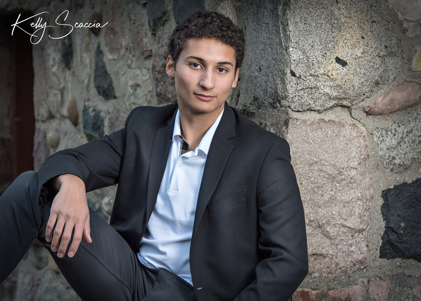 Outdoor senior guy portrait with short, dark, curly hair, wearing black sport coat, white shirt and jeans, serious expression and looking at you