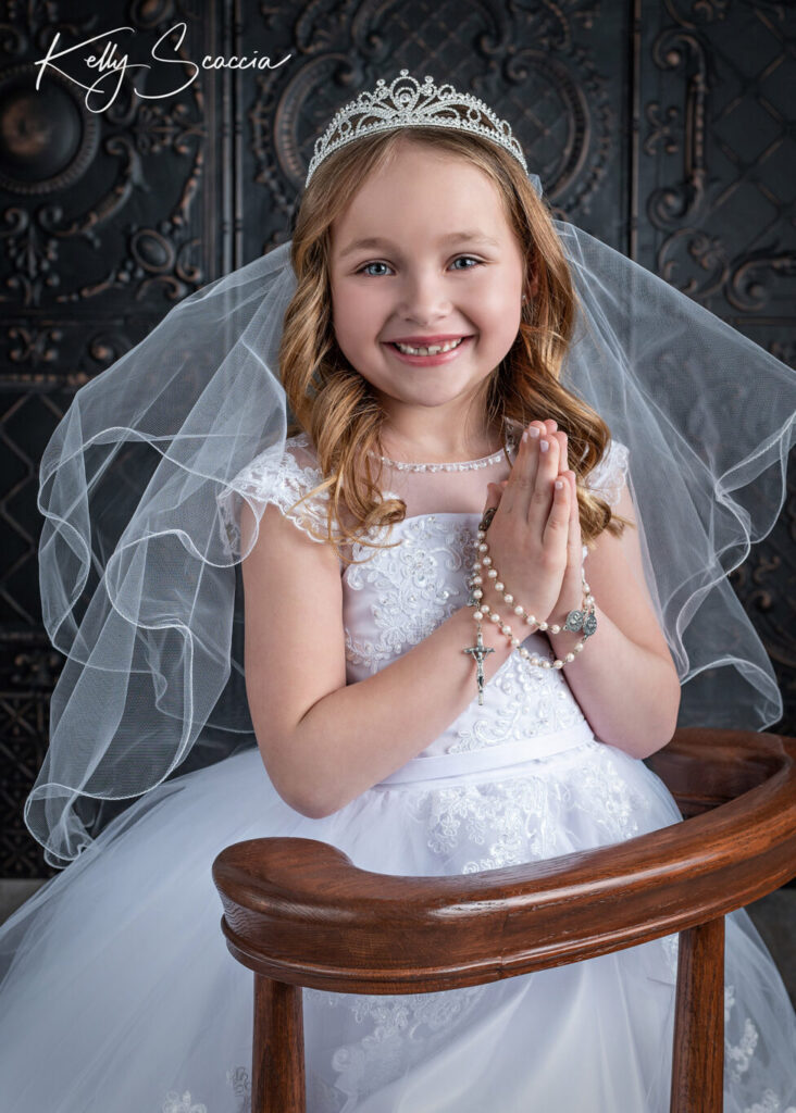 Studio communion girl portrait wearing white dress and tiara, smiling looking at you