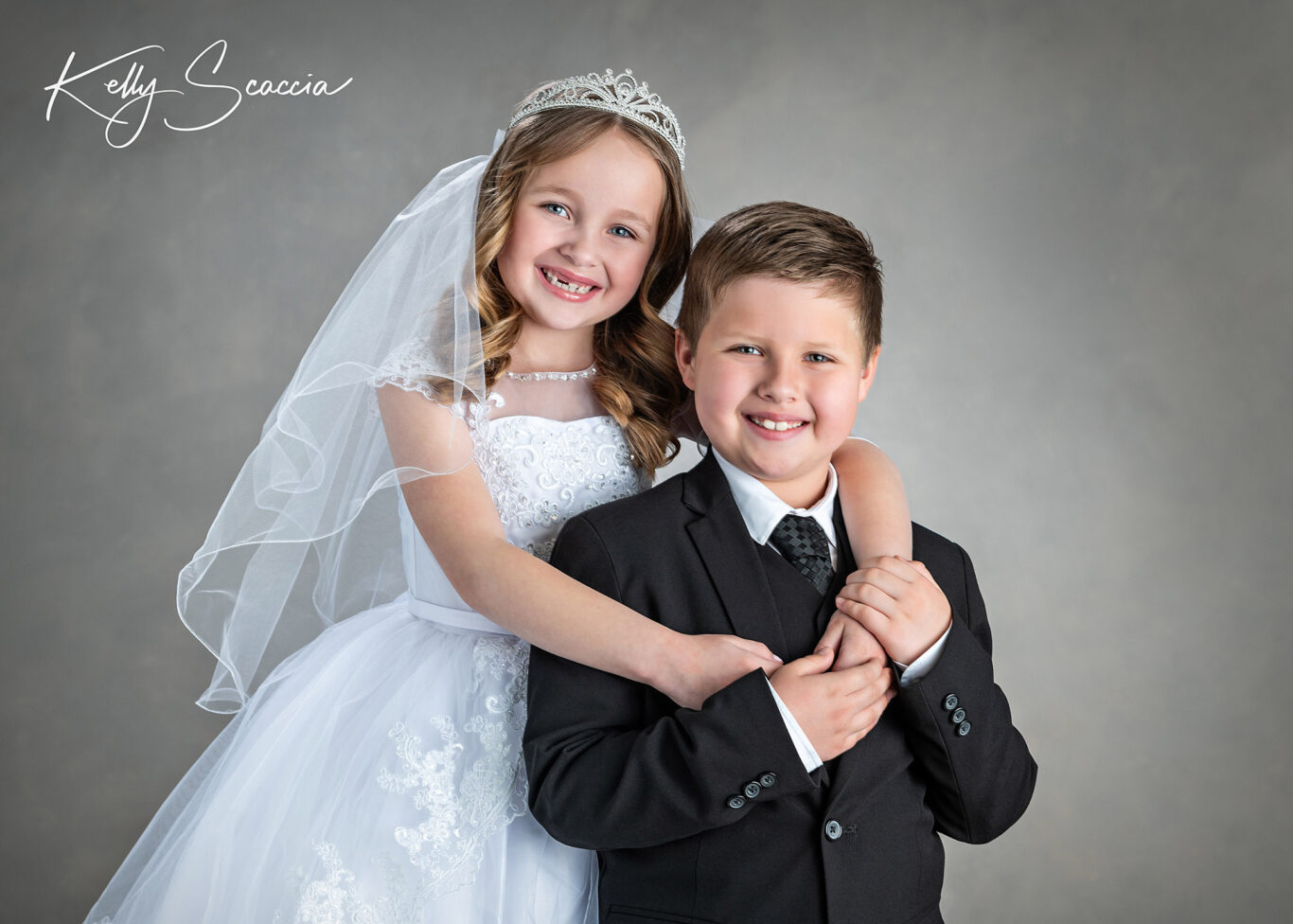 Brother and sister communion portrait wearing traditional white dress and black suit, smiling, looking at you