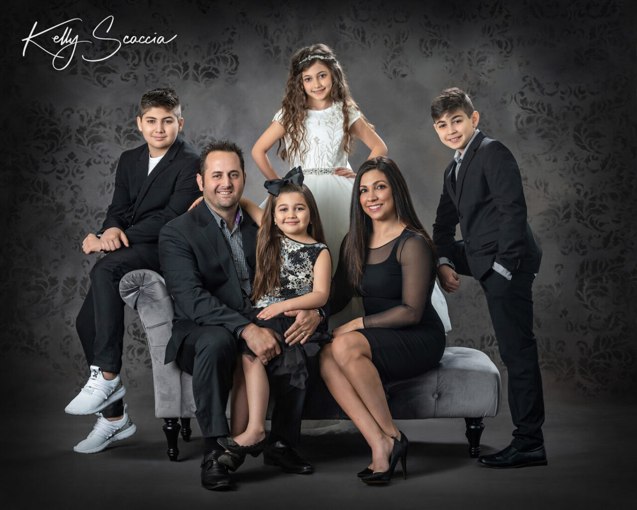 Formal family studio portrait of six in black and white clothing sitting on a couch