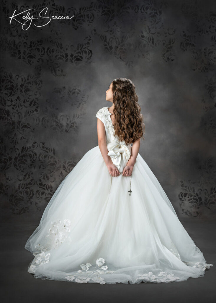 Studio communion girl portrait wearing formal gown and rhinestone tiara holding her rosary looking up at light serious expression