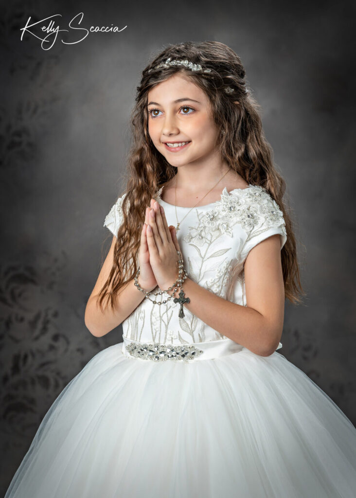 Studio communion girl portrait wearing formal gown and rhinestone tiara holding her rosary looking up and smiling