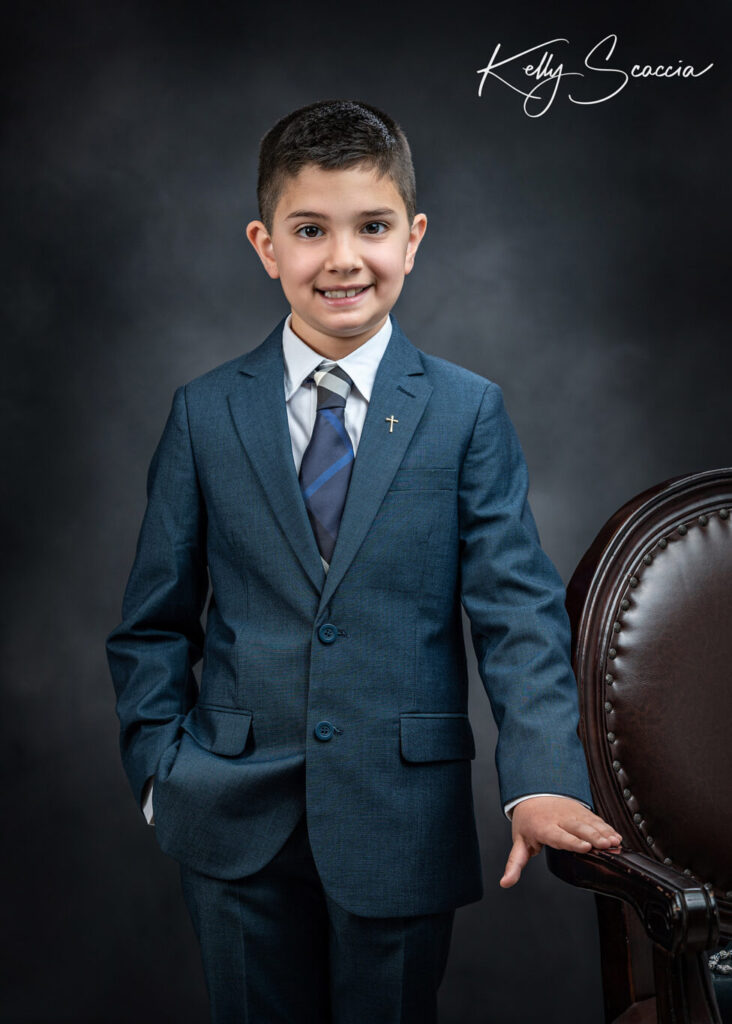 Formal communion boy studio portrait wearing blue suit, holding rosary, smiling, looking at you