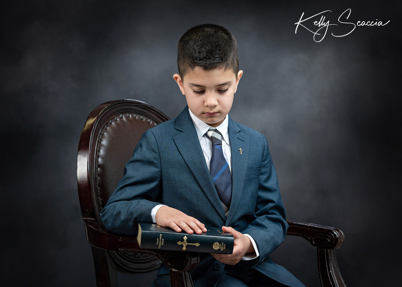 Formal communion boy studio portrait wearing blue suit, holding rosary, serious expression looking at you