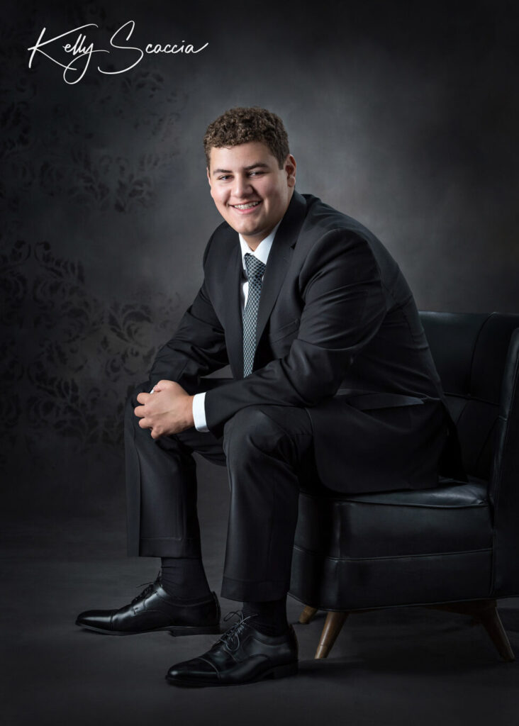 Senior guy studio portrait, dark, curly hair, looking at you, smiling, wearing a black suit