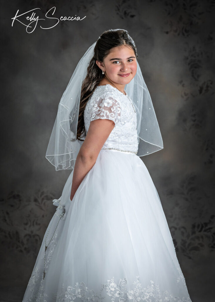 Communion girl in studio wearing traditional white dress, veil, holding rosary, smiling and looking at you
