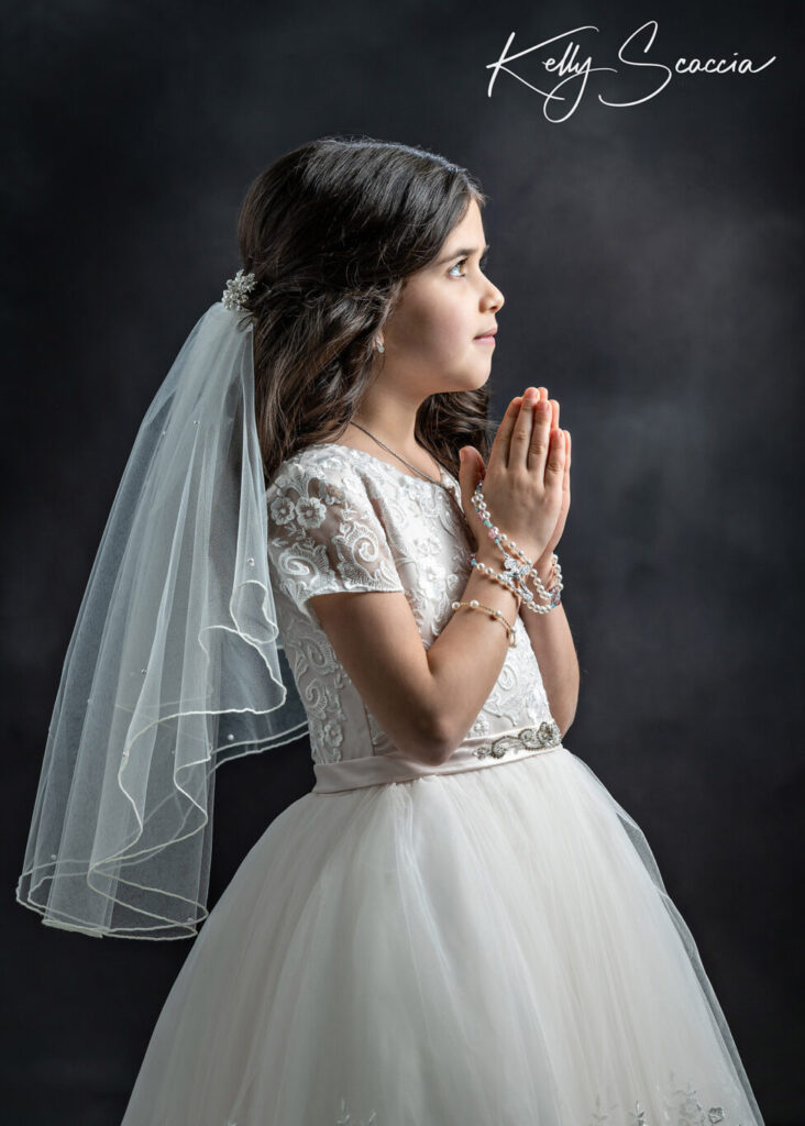 Studio communion girl portrait wearing traditional white dress, veil, crown and rosary in hands with a smile on her face looking up with hands in prayer