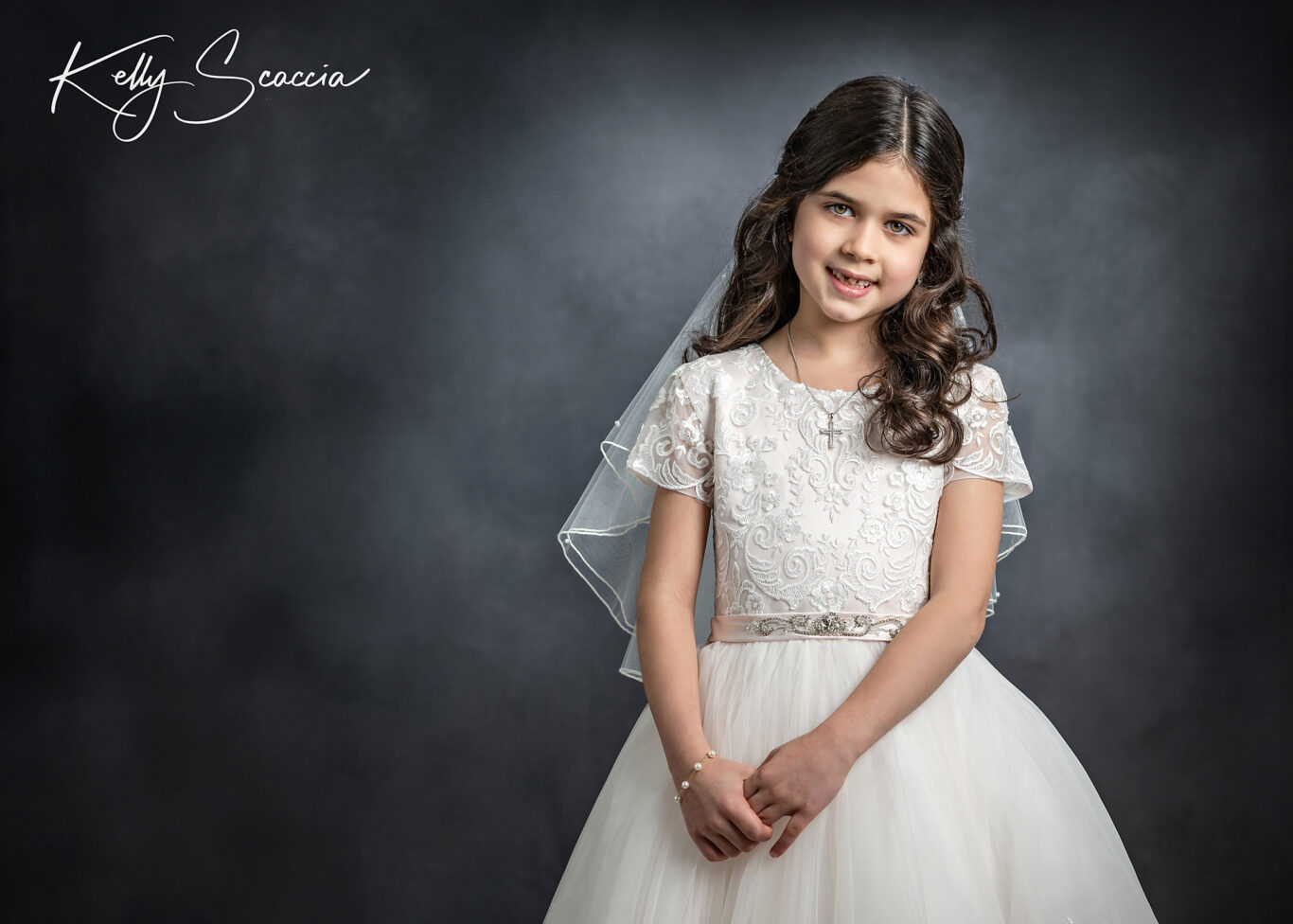Studio communion girl portrait wearing traditional white dress, veil, crown and rosary in hands with a smile on her face looking at you