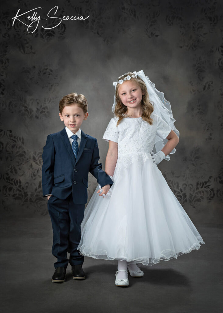 Communion studio portrait of girl with her little brother, both smiling and looking at you holding hands