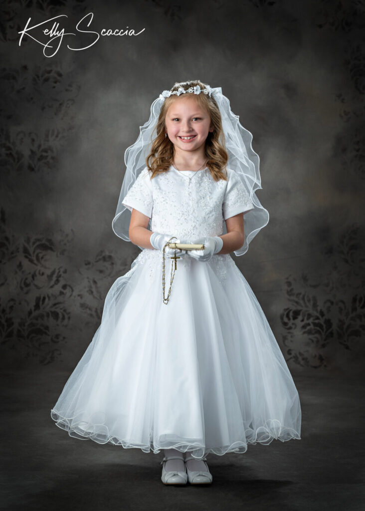 Communion studio portrait of girl in traditional white gown, holding rosary, smiling, looking at you