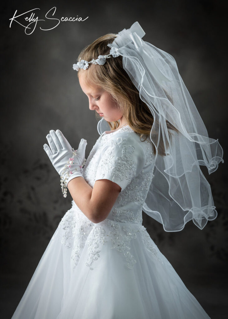 Communion studio portrait of girl in traditional white gown, holding rosary, serious expression, looking down at her hands in prayer