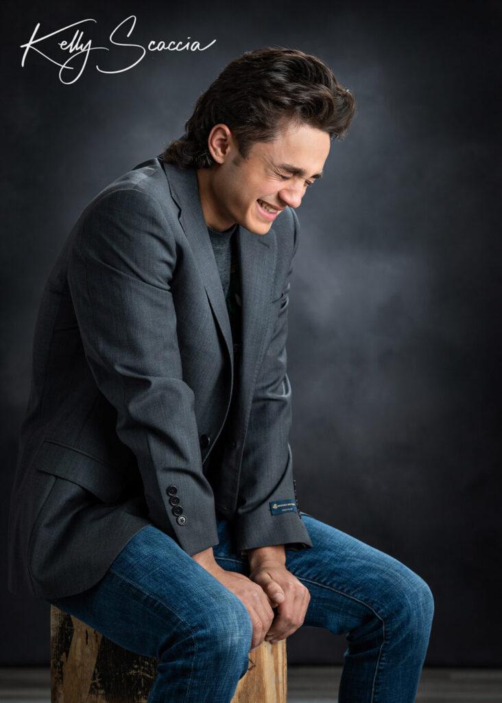 Senior guy studio portrait wearing jeans, black tshirt, gray sport coat, looking down, laughing