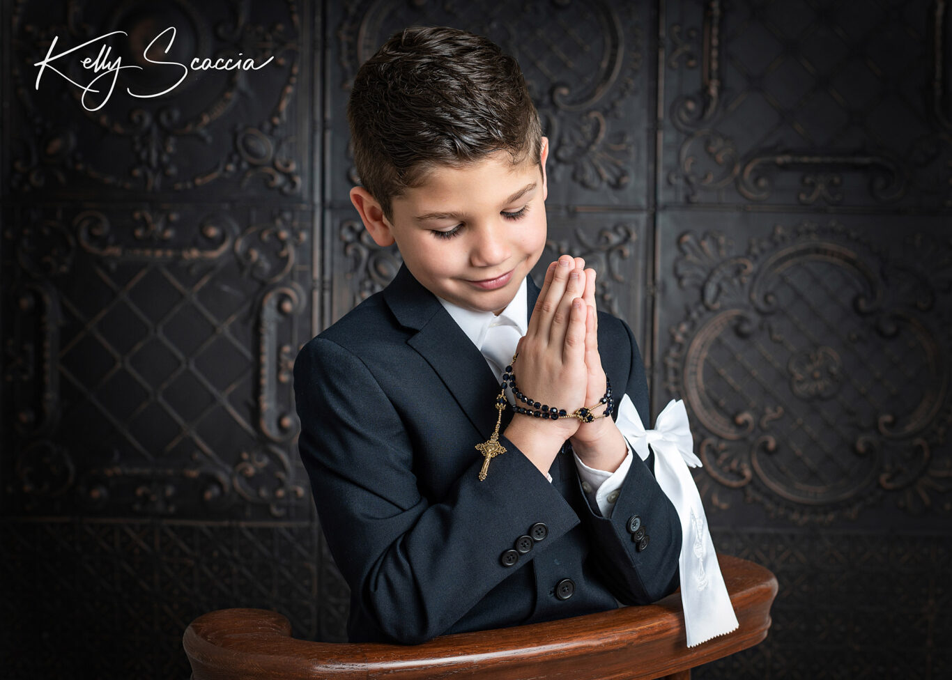 Studio communion boy portrait wearing a dark, navy suit, white bow on arm, holding his rosary, smiling, looking at his hands