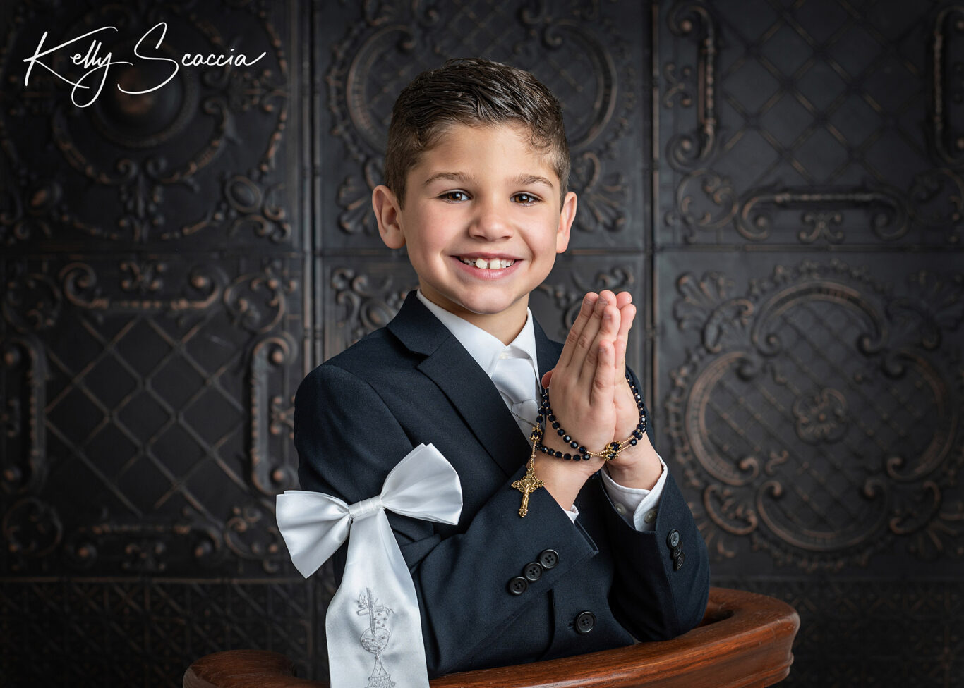 Studio communion boy portrait wearing a dark, navy suit, white bow on arm, holding his rosary, smiling, looking at you