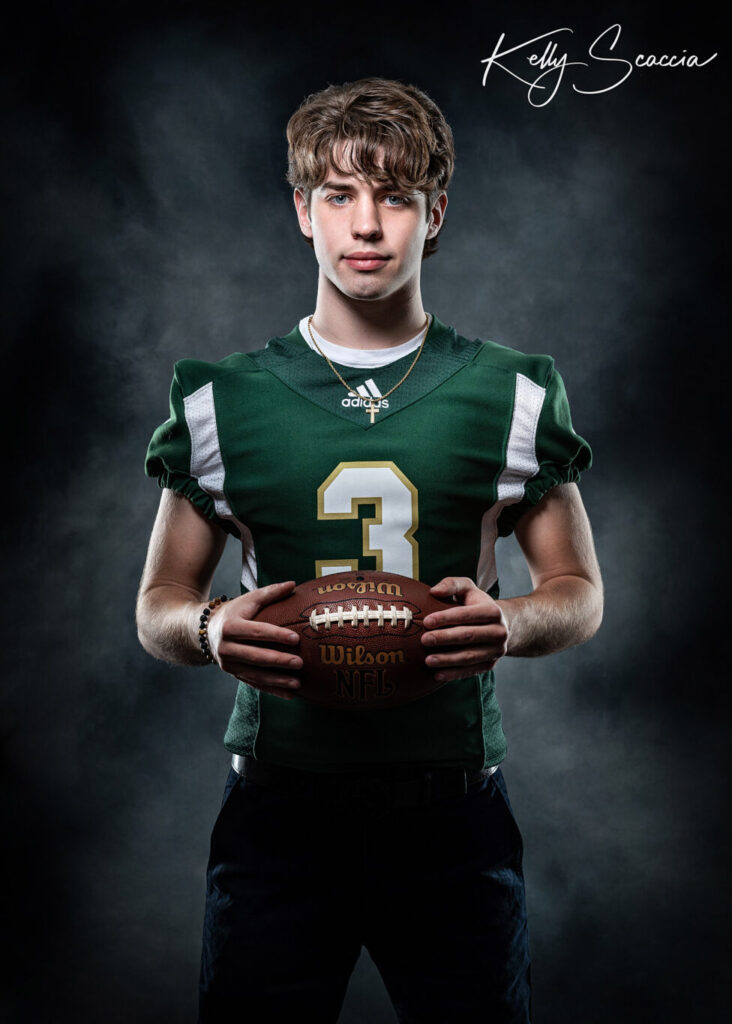 Studio senior guy portrait wearing blue pants and green football jersey, looking at you, serious expression, holding football