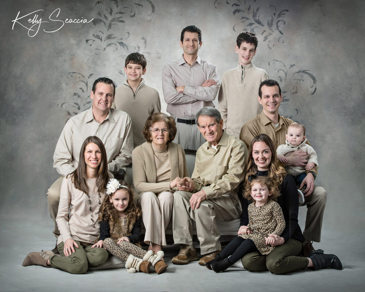Studio portrait of grandma and grandpa with five grandchildren, three kids, two with spouses, wearing brown tones, sitting on a couch, smiling looking at you