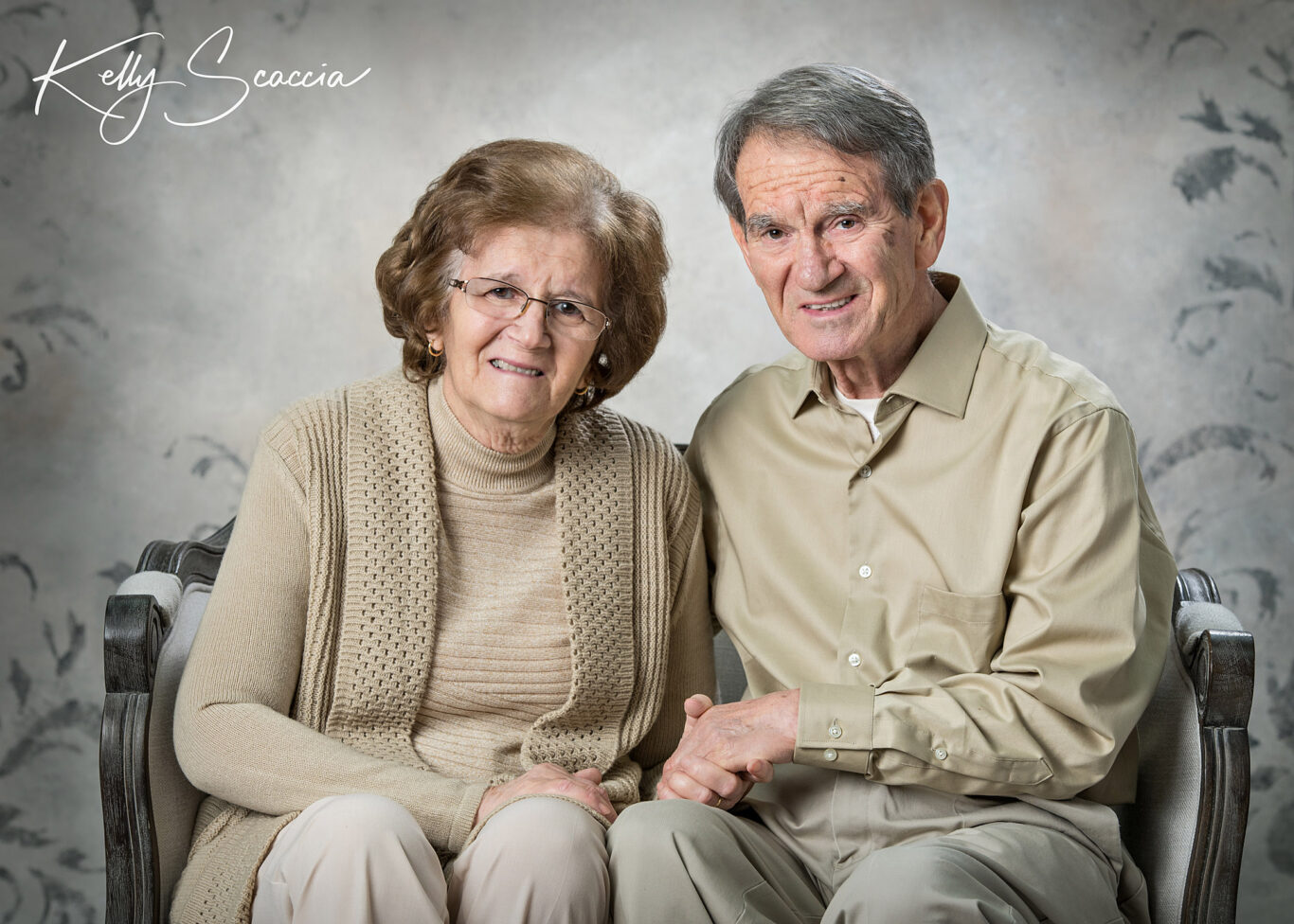 Studio portrait of grandma and grandpa, wearing brown tones, sitting on a couch, smiling looking at you