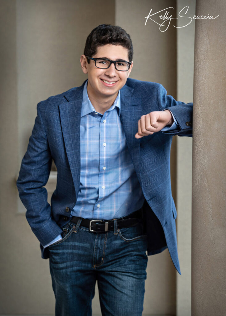 Outdoor senior guy portrait wearing blue sportcoat, blue shirt, jeans, smiling, looking at you