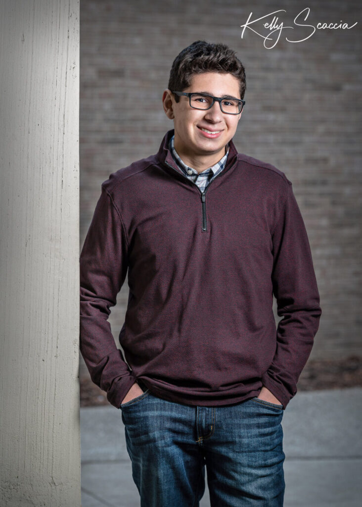 Outdoor senior guy portrait wearing plum sweater, jeans, smiling, looking at you