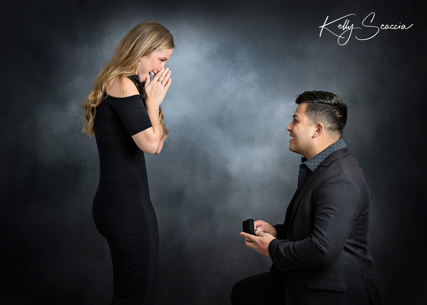 Studio engagement portrait of man with dark hair, dark pants and shirt, woman with long, blonde hair, wearing black short cocktail dress surprising her on his knee with ring in box