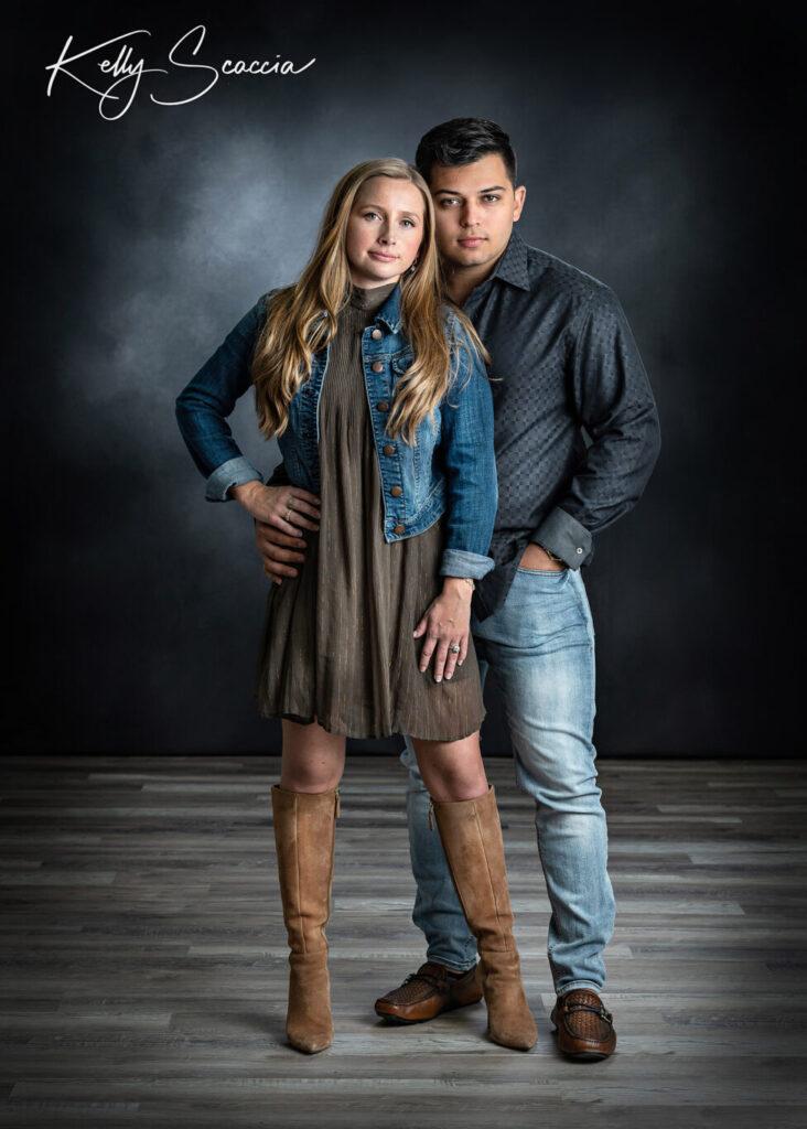 Studio engagement portrait of man with dark hair, wearing jeans and dark button down, woman wearing short brown dress with denim jacket, tall, brown boots with long, blonde hair
