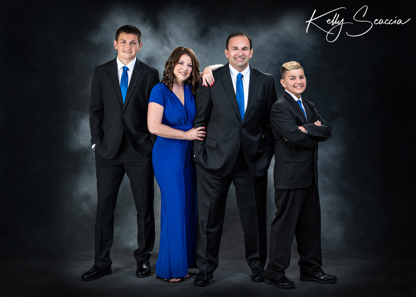 Formal studio portrait of wife in royal blue dress, husband in dark suit, blue tie, two teenage sons wearing matching suits with dad, all looking at you, smiling
