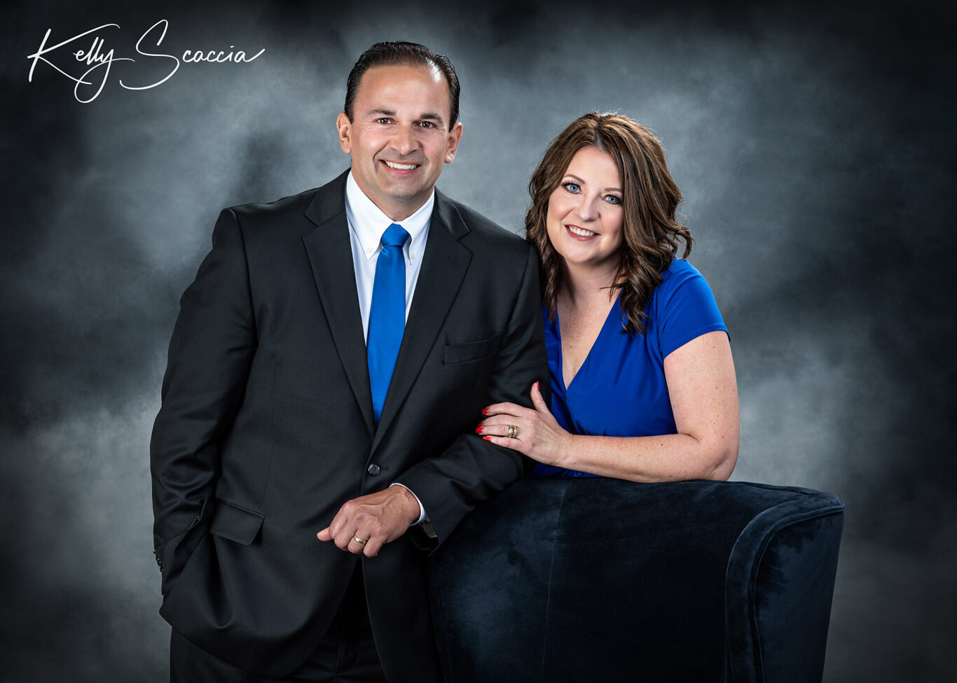 Formal studio portrait of wife in royal blue dress, husband in dark suit, blue tie, looking at you, smiling