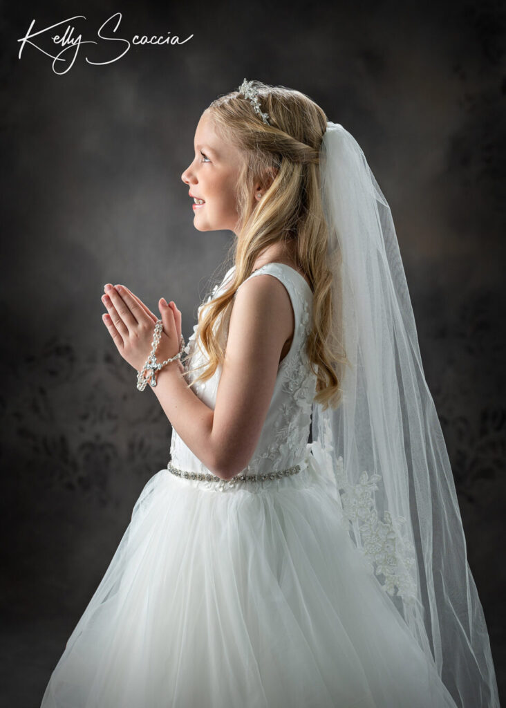 Studio communion portrait of little girl in formal white dress, veil and crown, smiling, hands in prayer, looking up at light